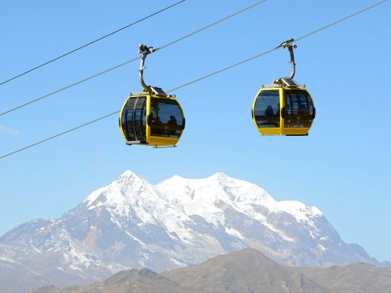 Bolivians use the yellow cable car line to make their way from El Alto, located at an altitude of 4,000 m above sea level, to the city centre of La Paz, Bolivia, 07 July 2015. Illimani, a local mountain of La Paz, is pictured in the background. Photo by: Georg Ismar/picture-alliance/dpa/AP Images